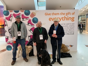 Graham Fraser and Bill standing with the two guide dogs Mercer and Toffee in front of the info stall.