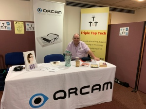Ian from orcam sitting behind a table that contains the OrCam device and marketing materials.